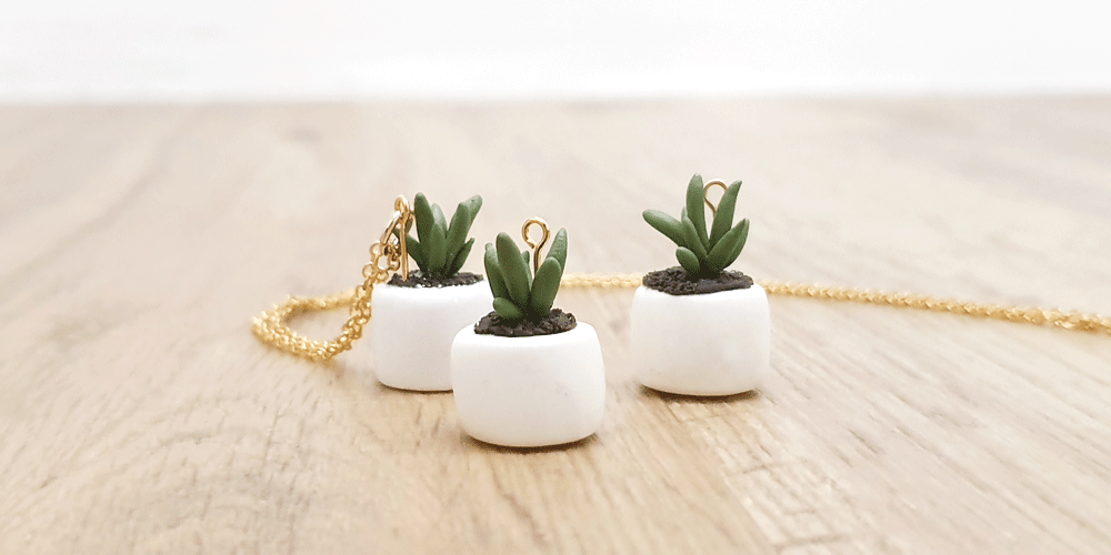 green succulents cactus plant in white pot nature polymer gold necklace