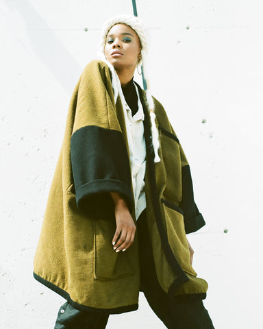Female model wearing an upcycled military blanket coat by Neoteny Apparel