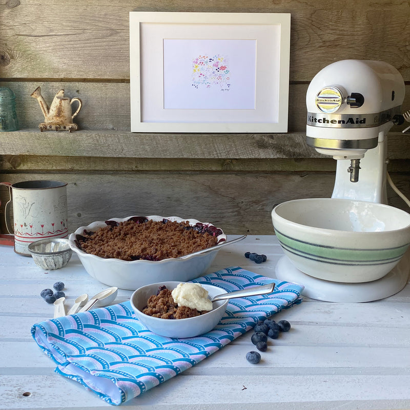 a blueberry crumble in a white pie dish, a small bowl of blueberry crumble with whipped cream, on a rustic white table with a blue fish scale patterned tea towel and stand mixer to the side