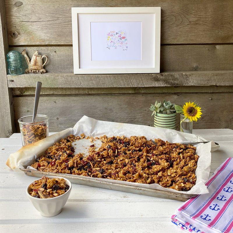 sweet and salty cherry-almond granola in a sheet pan on a rustic tabletop