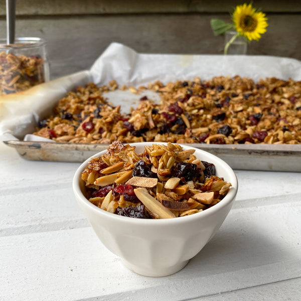 a small bowl of cherry-almond granola on a rustic tabletop