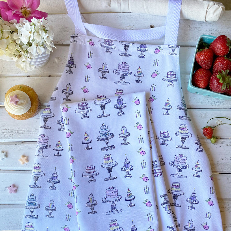 100% cotton eco-friendly bib apron with cute cakes and cupcakes pattern on a rustic wood wall