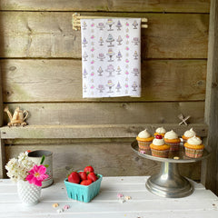 100% cotton eco-friendly tea towel / kitchen towel with cute hand drawn and painted cake and cupcake pattern on a rustic white table