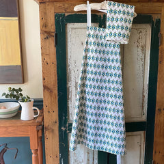 100% cotton eco-friendly bib apron with cute watercolor leaves and berries pattern on a rustic painted cabinet