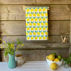 100% cotton eco-friendly tea towel / kitchen towel with cheery hand painted lemon pattern on a rustic white table