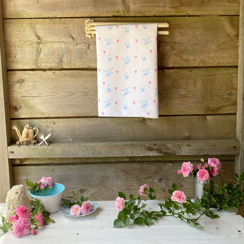 100% cotton eco-friendly tea towel / kitchen towel with cute pale blue skulls and pink hearts pattern on a rustic white table