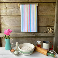 100% cotton eco-friendly tea towel / kitchen towel with a hand drawn pastel stripe pattern on a rustic white table