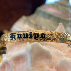 Baby Hawaiian heirloom bracelet with straight edge and black lettering.
