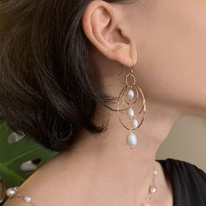 Four pearl triple hoop earring on model.