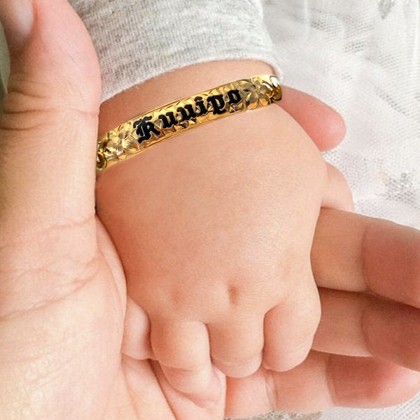 Baby Hawaiian heirloom bracelet with straight edge and black lettering on baby model.