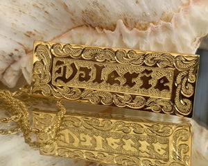 Nameplate with straight edge and raised gold lettering.