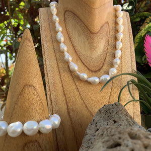 Baroque pearl necklace shown in white next to bracelet.