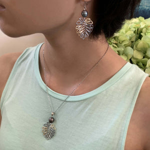 Monstera pearl pendant shown on model with earrings.