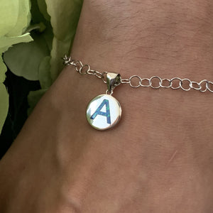 Opalite initial charm shown on model as a charm bracelet.