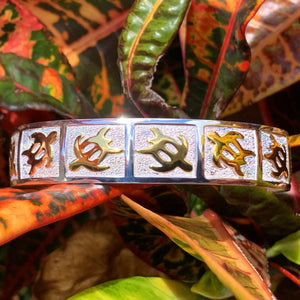 Close up of petroglyph honu cuff with gold honus in alternating directions on a pebble design background with a mirrored sterling silver base.