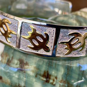 Extreme close up of petroglyph honu cuff with gold honus on a pebble design background with a mirrored sterling silver base.