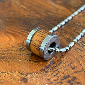 Koa tungsten barrel pendant close up.