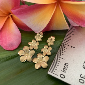 Plumeria flower 3 tier earrings next to ruler showing 1 inch.