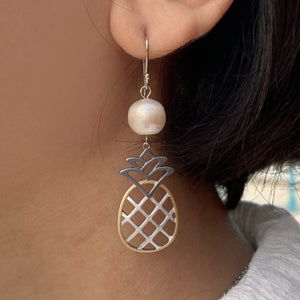 Close up of white pineapple pearl tri-color earrings on model