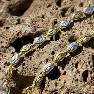 Close up of mooncut chain detail showing two tone colors of silver and gold alternating on the chain.