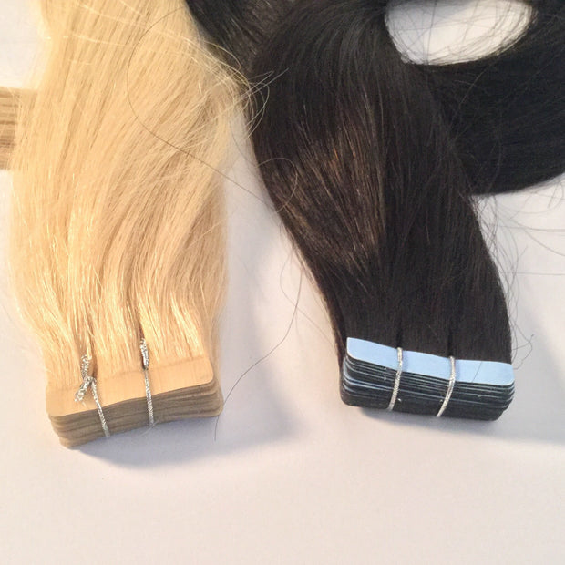 Blonde and brown tape hair extensions next to each other.