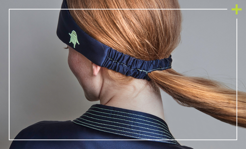 Woman wearing navy silk eye mask with elastic band and cutout hole for ponytail