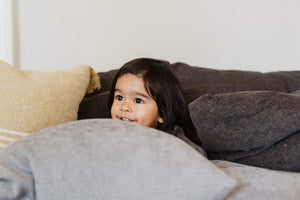 Girl Hiding behind the pillow