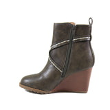A faux stacked wedge heel enhances the character of this stylish vegan leather bootie. Stay stylish no matter the season in a rich olive green vegan leather upper that features a stitched cross strap that covers the vamp. AR TIST by Diba London seals the deal with inside zipper entry, lug sole, and almond toe.
