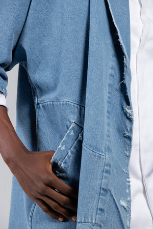 Welt pocket detail of Men's distressed denim kimono in a medium wash