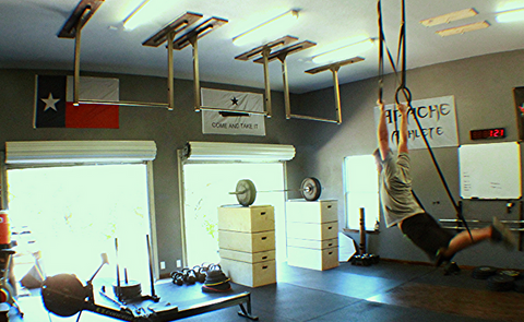 Kipping on wood gymnastics rings in a garage gym (onefitwonder)