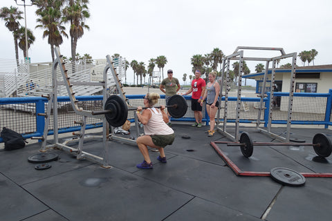 A woman squatting at Muscle beach