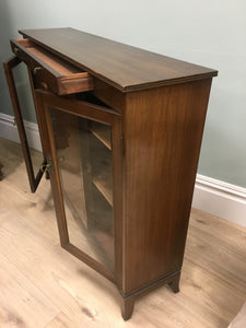 Unusually slim mahogany cabinet with single drawer above and three opening doors and shelves