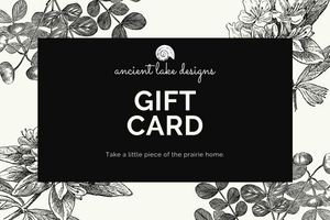 "Gift Card showing Ancient Lake Designs logo with shell at top and reads ""Take a little piece of the prairie home."" Black and white botanical print around perimeter."