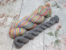 Load image into Gallery viewer, Silver Sparkle Self Striping Yarn in Rainbows and Stormclouds colourway with a coordinating mini skein