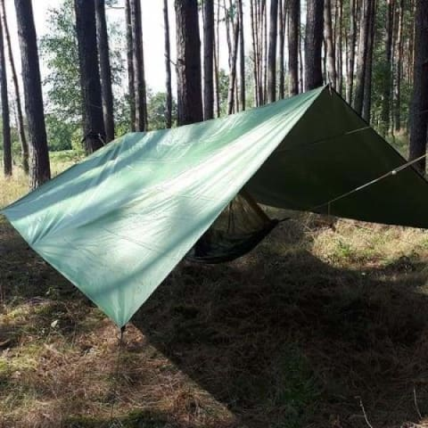 a green tent on a wooden surface