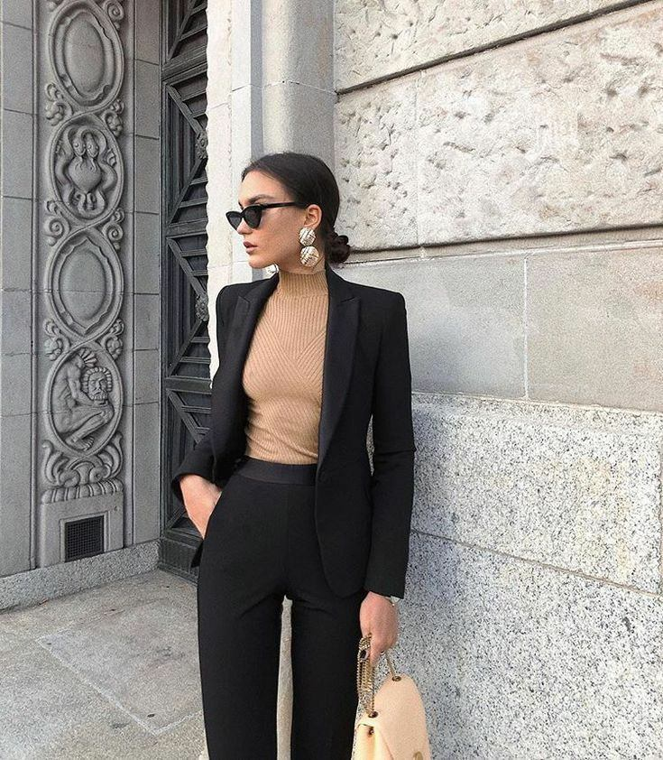A beige ribbed bodycon turtleneck paired with a black straight blazer and classic bodycon black pants.