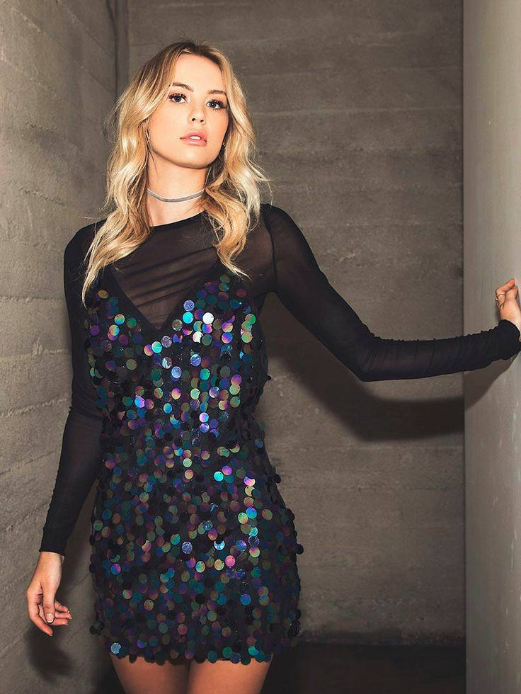 A black sheer collarless turtleneck paired with a bold mini sequin cocktail dress.