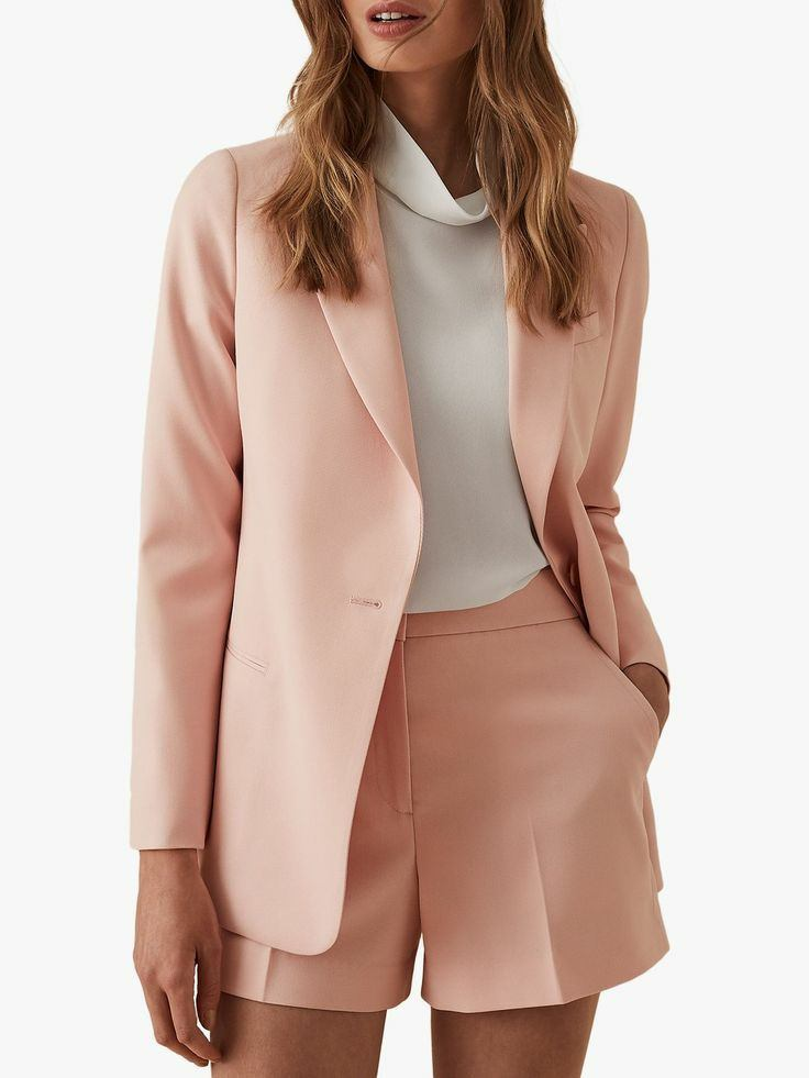 A white turtleneck with a free collar paired with a pale pink straight-cut blazer and short, high-waisted oversized shorts.