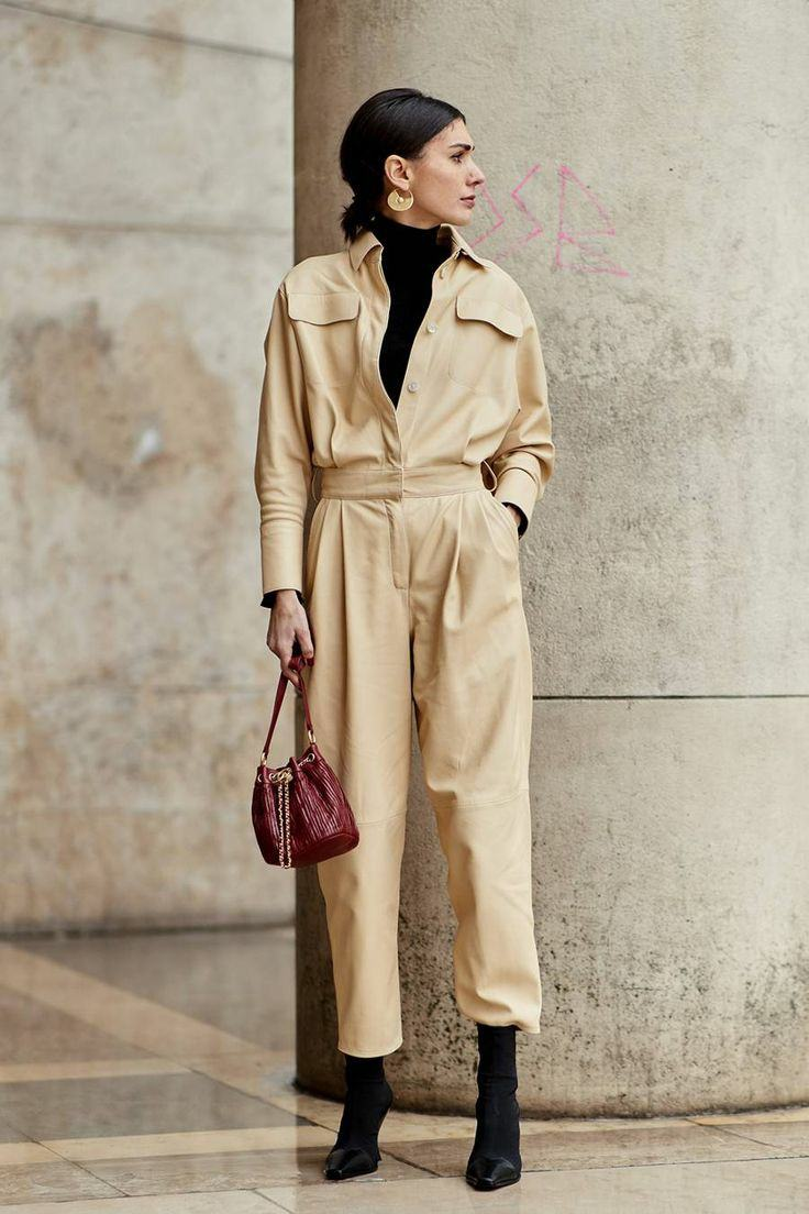 A beige work suit with decorative pockets and a deep cut in combination with a black turtleneck, black suede ankle boots with a leather nose, a red bag.