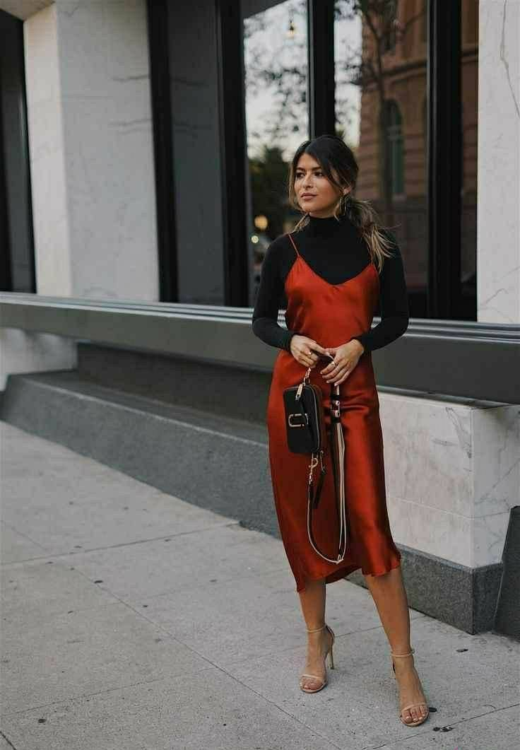 Black bodycon turtleneck combined with a silk red dress below the knee and with thin straps
