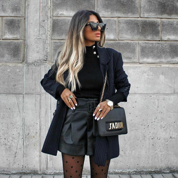 A black, form-fitting turtleneck with a decorated metal button collar paired with oversized black leather shorts with a gathered high waist in a black blazer with white stripes. The image is complemented by accessories: a black belt bag, rings, watches and black glasses.