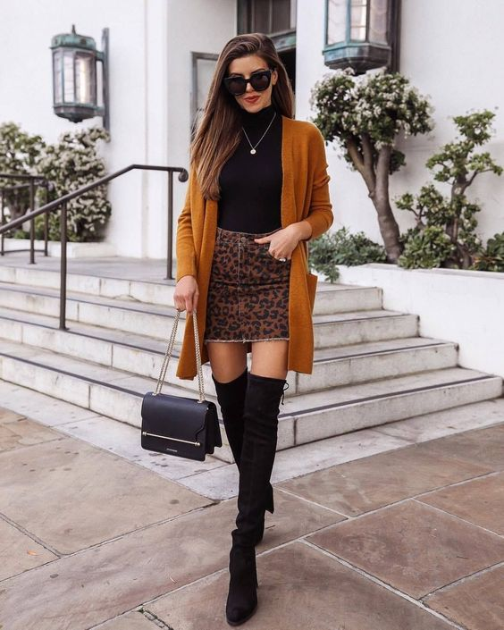 A black, tight-fitting turtleneck paired with a leopard-print denim dark brown mini skirt and fitted suede over the knee over the knee boots with heels and lace-ups. The image is complemented by accessories: a black clutch bag, black glasses and a chain.