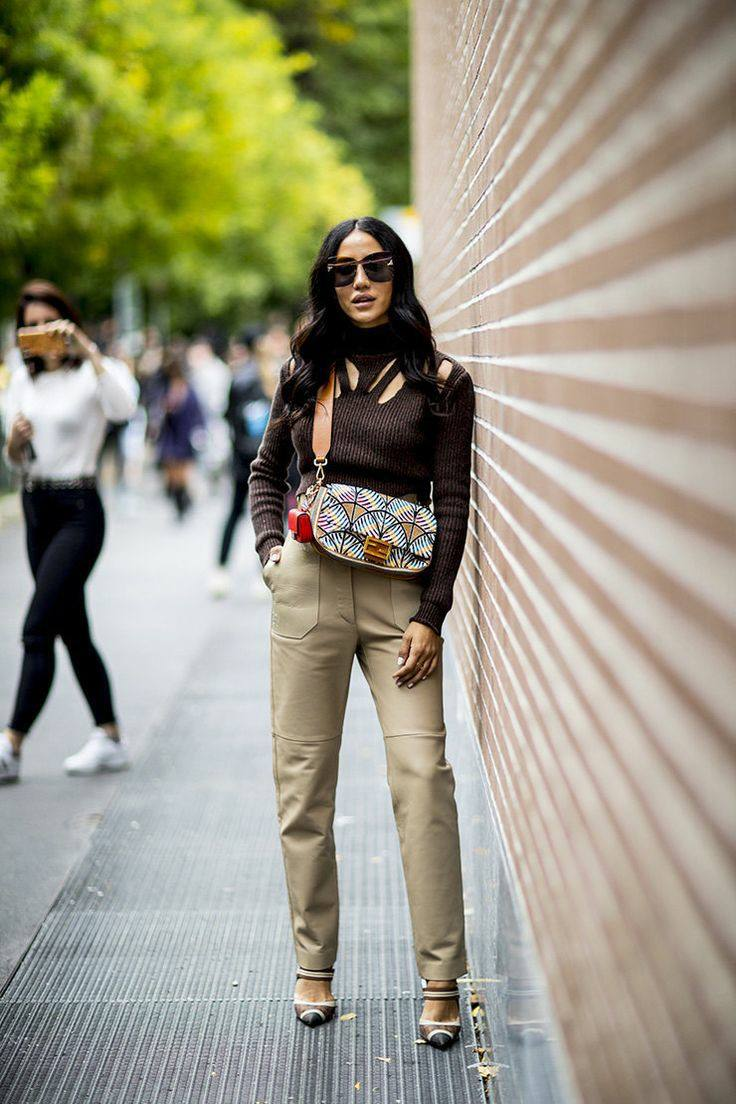 Dark brown turtleneck with a neckline and cutouts on the chest paired with light straight leather pants