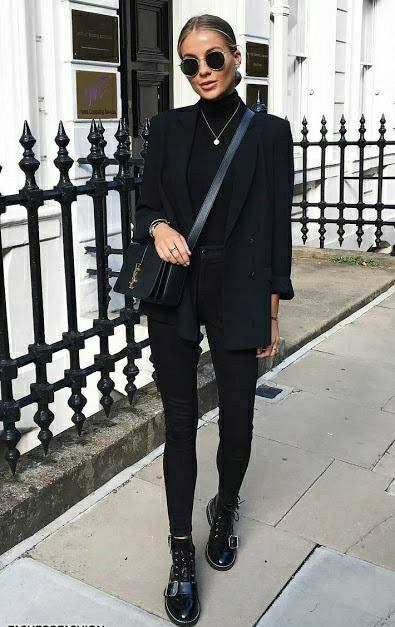 Girls have a black total look: a turtleneck with a high neck, high-waisted skinny jeans, an elongated straight-cut jacket, lace-up boots with straps, a square belt bag, round glasses and a thin chain.