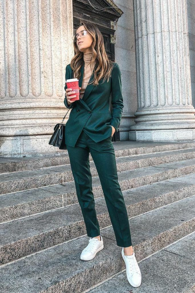 The girl is wearing a beige turtleneck with a long collar, an emerald-colored suit: tight-fitting trousers and a fitted jacket, white sneakers, a black leather belt bag.
