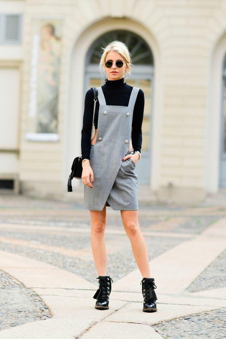The girl is wearing a black basic turtleneck, a gray wrap sundress with white buttons and a square neckline, black leather lace-up boots.