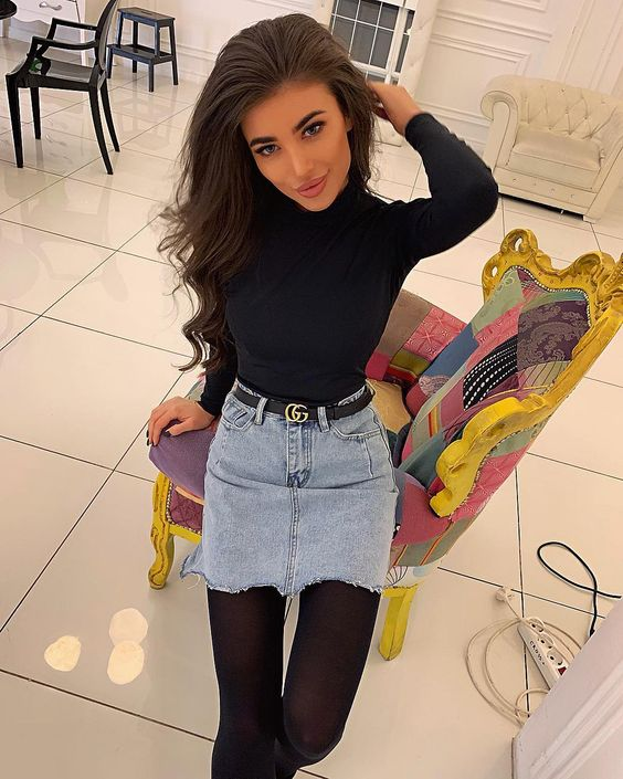 The girl is wearing a thin black turtleneck, a light blue denim mini skirt with a black leather belt, tight black tights.