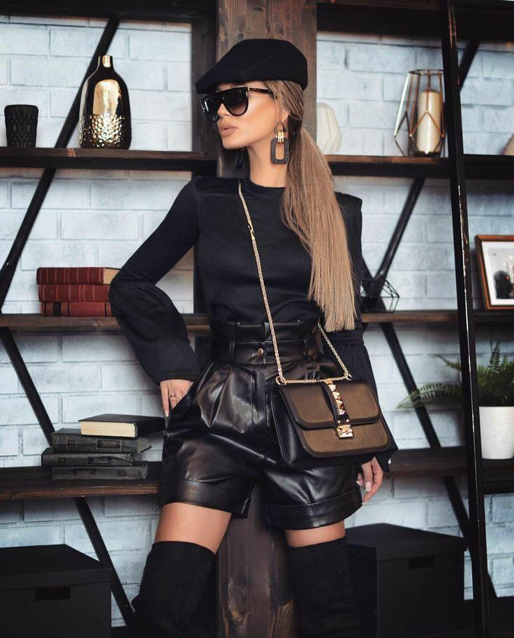 The girl is wearing a black tight-fitting turtleneck without a collar and with puffy sleeves, loose leather shorts with a high waist, suede over the knee boots, a black square belt bag, a black cap, bulky earrings and glasses.