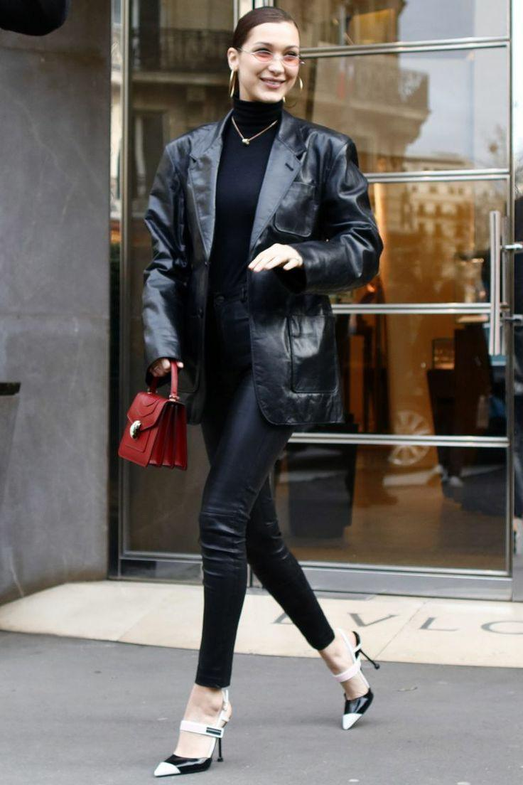 The girl is wearing a black turtleneck with a collar, leather tight pants, an oversized leather black jacket, black and white pumps with a pointed toe and thin heels, a red small square bag, a thin chain, light pink round glasses and earrings.
