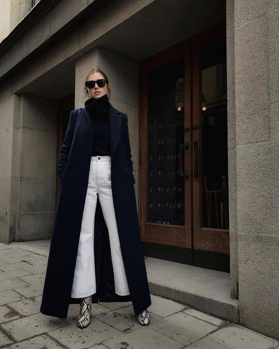 The girl is wearing a black turtleneck with a voluminous neck, white bell-bottomed jeans, boots with a crocodile print with high thick heels, a dark blue oversized maxi coat, black square glasses.